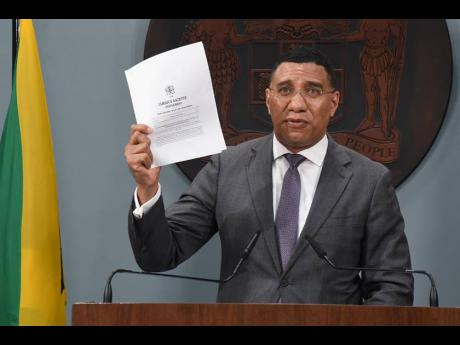 Prime Minister Andrew Holness displays the gazetted order declaring Norwood a zone of special operations on Sunday. Holness was addressing a Jamaica House press conference.