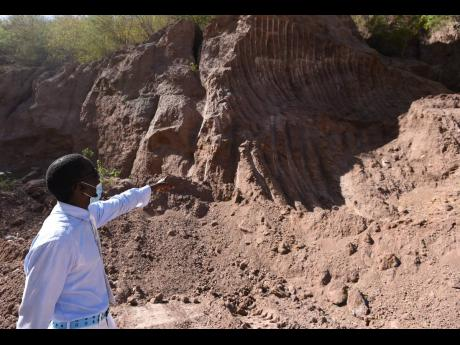 Kirk Patterson points to a mountain of silt build-up which he blames on mining activity.