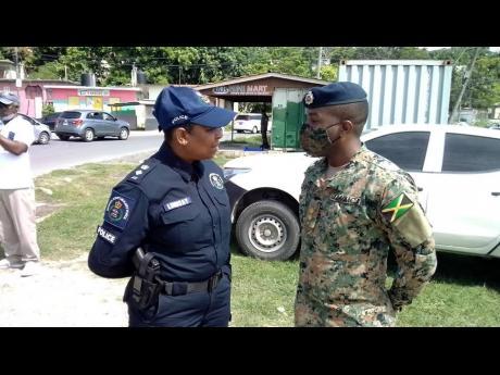 Police spokesperson Senior Superintendent Stephanie Lindsay having dialogue with Lieutenant Nathan Curtis, public relations officer for the Jamaica Defence Force, in Norwood, St James, on Sunday. Norwood has been declared a ZOSO.