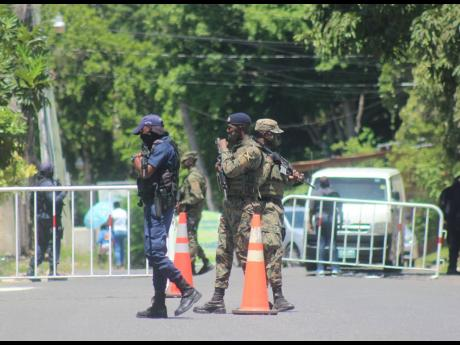 Police and soldiers man a security checkpoint yesterday at the entrance to the Norwood community in St James, where a zone of special operations is was declared on Sunday.