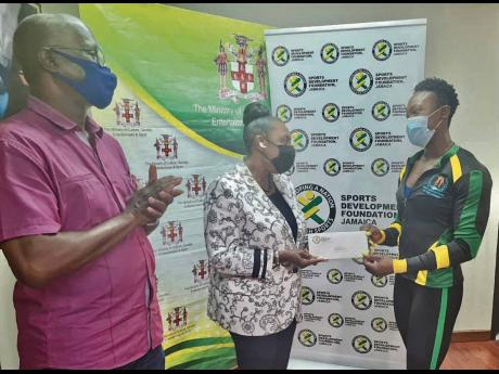 Sport Minister Olivia Grange (centre) presenting bodybuilder Kristen McGregor with a cheque of $250,000 from the Sports Development Foundation (SDF) to assist her in making the trip to The Bahamas to compete at the Puerto Rico Pro Olympia Qualifier. Sharin