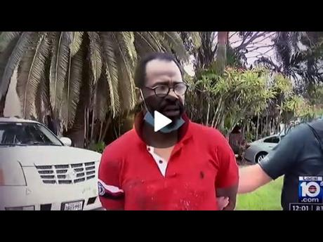 """Dean Cooke, also known as 'Boobie Speng', is the bespectacled man in handcuffs in the viral video who told a Florida television station that he """"really want to leave because no life is in Jamaica right now""""."""