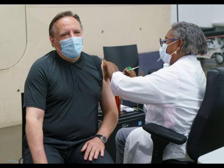 Quebec Premier Francois Legault receives his second dose of the Pfizer vaccine from Regine Laurent, former president of the Fédération interprofessionnelle de la santé du Québec, at a COVID-19 vaccination clinic in Montreal yesterday.