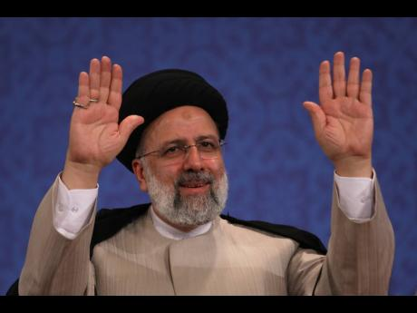 Iran's new President-elect Ebrahim Raisi waves to participants at the conclusion of his press conference in Tehran, Iran, yesterday.