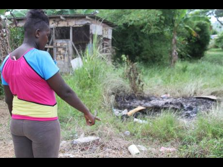 Melissa Mason looks at an an area where the blood-stained mattress, pillows and sheets were burnt yesterday after her friend Tashika McKay was allegedly killed by her boyfriend in Rhoden Hall, Kellits, Clarendon, on Sunday.