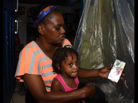 Lorraine Mendez holds her three-year-old granddaughter Chloe Saunders as they speak to Mendez's daughter, 30-year-old Trishauna Blair, who survived a February 17 motor vehicle crash on South Camp Road that claimed the life of one person. Blair has been h