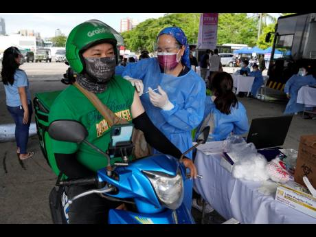 A food delivery driver is inoculated with China's Sinovac COVID-19 vaccine at a drive-thru vaccination centre in Manila, Philippines, yesterday.