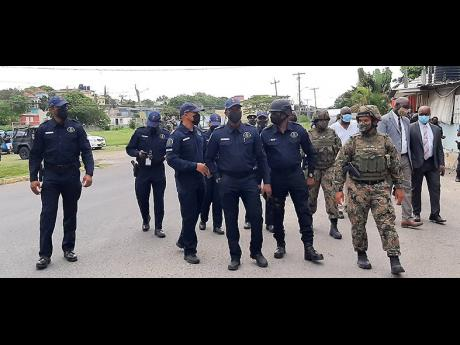 Commissioner of Police Major General Antony Anderson (third left) surrounded by members of the security forces during his tour of Norwood on Tuesday.