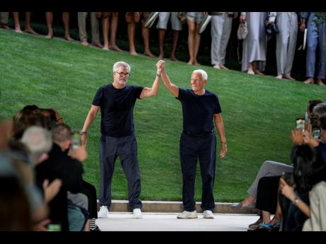 Giorgio Armani (right) and Leo Dell'Orco accept applause at the conclusion of the Giorgio Armani men's Spring Summer 2022 collection, in Milan, Italy, on Monday.