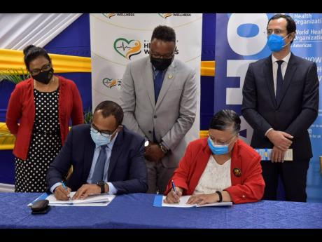 Minister of Health and Wellness Dr Christopher Tufton (seated at left) and Country Representative in  Jamaica for the Pan American Health Organization (PAHO)/World Health Organization (WHO), Dr Bernadette Theodore-Gandi, sign a technical assistance agreeme