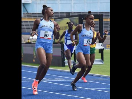 Tina Clayton (left) looks over at her twin sister Tia Clayton (right) as they cross the finish line in the  100 metres ahead of Thennel Williams (right) and Kacy-Ann Johnson (second left) during the JAAA All Comers meet at the National Stadium on Saturday,