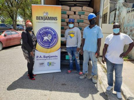 P.A. Benjamin donated bags of cement to family members who lost their home in an early-morning fire on March 8. Over 30 families were displaced. They were not able to save anything but their lives. Lisa Andrade-Thompson (left), marketing manager, food and