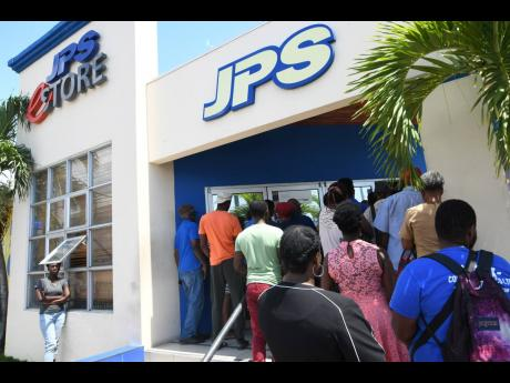 Customers lined up awaiting service at the JPS Ruthven Raod branch in Kingston on March 23, 2020, days after the coronvirus pandemic was detected in Jamaica and social distancing protocols began taking effect.