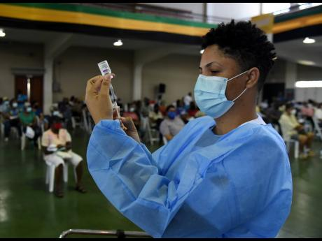 Sasha Johnson, a registered midwife, prepares to administer the Oxford-AstraZeneca COVID-19 vaccine for persons 50 and older who turned out for their second dose at the National Arena on June 19. Regional countries, including Jamaica, lag the developed wo