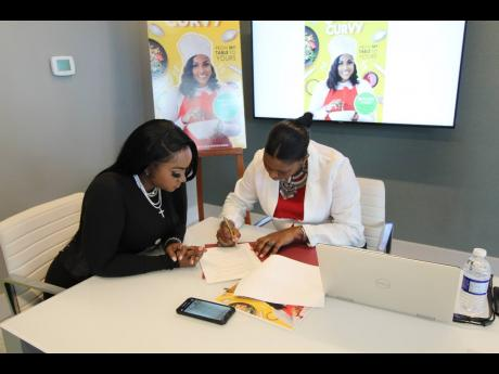 Yanique 'Curvy Diva' Barrett (left) looks on as Ingrid Abrahams Larmond, COO of Pageturner, signs the document.