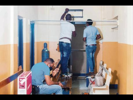Volunteers prepare to install the donated television set in the Cardiology Unit, Kingston Public Hospital.