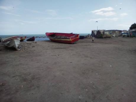 A man walks past boats beached at the Old Harbour Fishing Village, St Catherine.