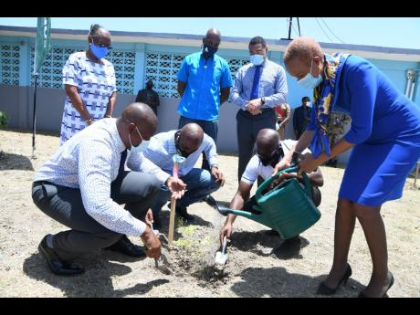 Standing (from left): Sharon Dale, chairman, St Catherine High School Board; Ainsley Henry, CEO and conservator of forests, Forestry Department; and Prime Minister Andrew Holness looking while (stooping, from left) Principal Marlon Campbell; Dr Andrew Whea