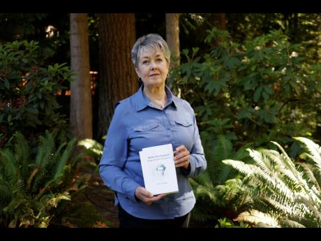 Karen McKnight stands in her backyard last Saturday in Sammamish, Washington, holding two books written by her brother Ross Bagne of Cheyenne, Wyoing. Nearly all COVID-19 deaths in the United States now are in people who weren't vaccinated like Bagne, a