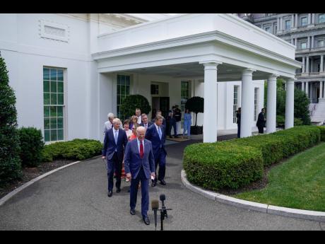 President Joe Biden (in front) walks out of the White House with senators to speak on Thursday, June 24, in Washington.