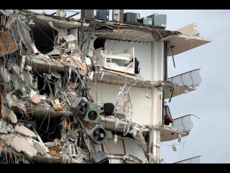 Items and debris dangle from a section of the oceanfront Champlain Towers South Condo that partially collapsed Thursday yesterday in the Surfside area of Miami, Florida.