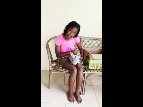 A younger Jones holds a pet rabbit. The young girl who simply loved all animals has come a long way, now hoping to pursue studies in Grenada and become a veterinarian.