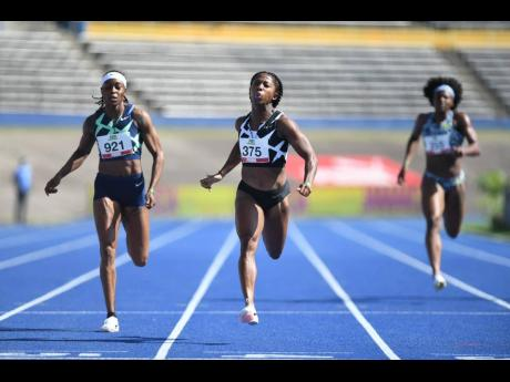 Shelly-Ann Fraser-Pryce crosses the line ahead of runner-up Shericka Jackson (not pictured), and Elaine Thompson Herah (left) to win the women's 200m final at the National Senior Championships at the National Stadium on Sunday morning.