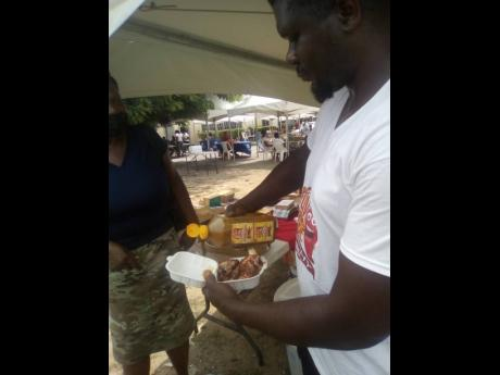 Howard Mathews pouring some of his Flava Fire Scotchy pepper sauce on a bit of chicken at the fair.