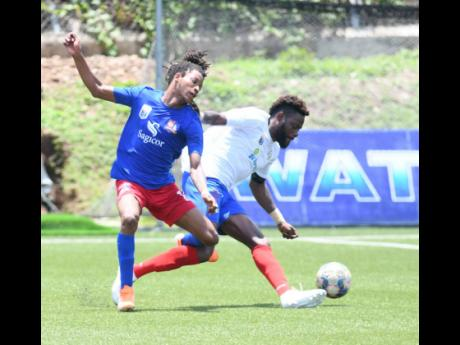 Portmore United captain and goalscorer Ricardo Morris (right) turns away from Dunbeholden's Kimoni Bailey in their Jamaica Premier League first round match held at the Captain Horace Burrell Centre of Excellence, at the UWI Mona Campus in St Andrew yeste