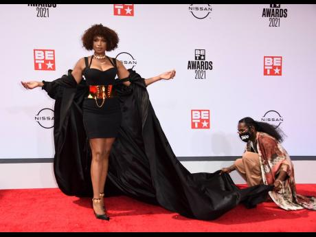 An assistant helps with Jennifer Hudson's outfit as she poses at the BET Awards at the Microsoft Theater in Los Angeles.