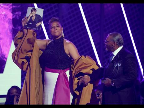 Queen Latifah, winner of the Lifetime Achievement Award, holds a photo of her late mother, Rita Owens, as she walks with her father, Lancelot Owens Sr, at the BET Awards on Sunday.