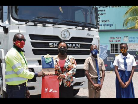 Fleet driver at Caribbean Cement Company Limited Curtis Guthrie (left) makes a presentation to the principal of Watsonton Primary School, Marchelle Williams-Hinds,, during a recent visit to the institution to promote road safety among members of the studen