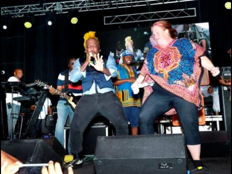 Elephant Man tries not to be upstaged by a patron who joined him on stage at the 2019 jerk festival.