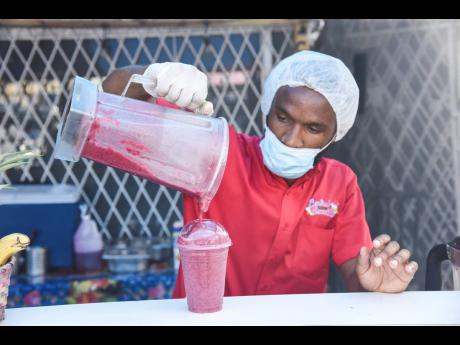 Owner of Central Smoothies, Lenard Christie, pours a freshly made Ali Berry crush, made with pineapple, blueberry and strawberry.