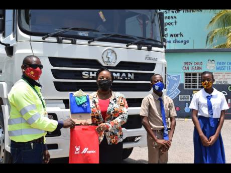 Fleet driver at Caribbean Cement Company Limited, Curtis Guthrie (left), makes a presentation to principal of the Watsonton Primary School in Clarendon, Marchelle Williams-Hinds (second left), during a recent visit to the institution to promote road safety