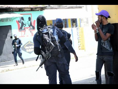 Police arrest a man while patrolling the streets of Arnett Gardens, south St Andrew, after a triple shooting in the community.