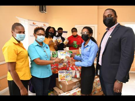 Members of the Employee Benefits Administration Division of Guardian Life Ltd donate non-perishable food items to Mustard Seed Communities, My Father's House. In the photo, Alicia Baggoo (second right), pensions administrator, and Oneil Clarke (right), v