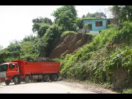 A crew contracted by the National Works Agency clearing a land slippage from the main road in Johnson Town, Hanover, on Wednesday. Residents in precariously perched homes say they have nowhere to go.