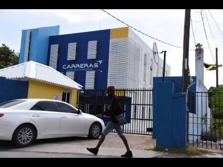 A pedestrian passes the Ripon Road, New Kingston, headquarters of Carreras on Wednesday. The cigarette distributor warns that draft tobacco legislation could imperil the gifting of scores of scholarships it issues annually.