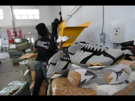 A worker at the Jamaica Customs Agency tosses counterfeit goods into a shredder at a state facility in Kingston on Wednesday.