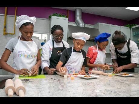 Students participate in a summer camp cooking activity inside the Nestlé Corporate Kitchen. The students are being helped by the YOCUTA chefs (young culinary talents) in preparing a quick and easy meal of their choice to encourage healthy eating habits.