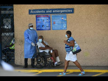 A patient is assisted at Kingston Public Hospital on Thursday. Hundreds of junior doctors across the island staged a sickout over a simmering contracts row, crippling services at many hospitals.