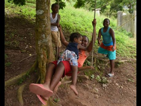 Two-year-old Sekani Henderson sits in nine-year-old Jayden Lindo's lap while they are both been pushed on a swing by eleven-year-old Jamari Lindo while five-year-old Jowain Henderson watches. The children had taken a break from online school to have a litt