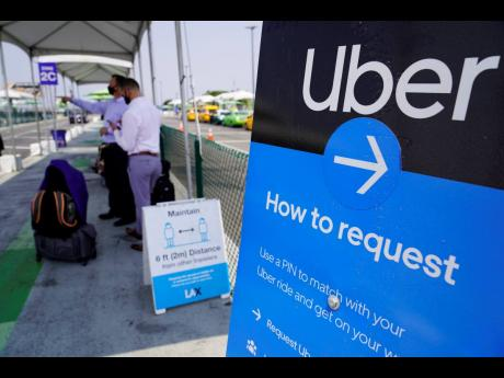 In this August 20, 2020, file photo travellers request an Uber ride at Los Angeles International Airport's LAX-it pick up terminal.