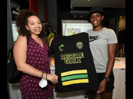 National striker Khadija Shaw poses with Ashley Codner (left) during a autograph session at the Western Sports store in Tropical Plaza, St Andrew, yesterday.