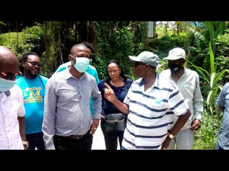 Minister without portfolio in the Ministry of Economic Growth and Job Creation, Everald Warmington (second right), addresses Westmoreland Central Member of Parliament George Wright during a tour of roads in the constituency on Wednesday, June 30. At right