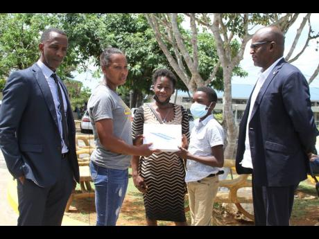 Avatar Muschette, grade-seven student of Clarendon College, Chapelton, accepts a tablet computer from Icylyn Green Whitfield of Pencils4Kids.  Looking on (from left) are Randy Griffiths, founder/president Pencils 4 Kids; Charmaine Warburton, Avatar's mot