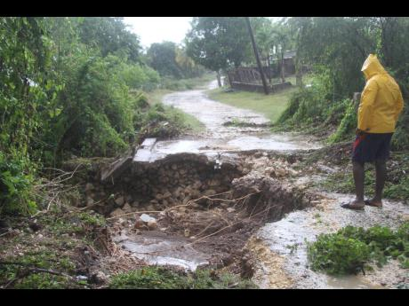 Denzil Hill of Gimme-Me-Bit surveys a collapsed road in the Clarendon community. He blamed the disaster on an unmaintained waterway.