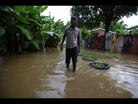 A boy walks through floodwaters in a yard in Bamboo River, Morant Bay, St Thomas, during the passage of Tropical Storm Elsa on Sunday.