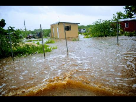 A flooded street in Old Harbour Bay, St Catherine, on Sunday. Preliminary reports indicate that St Catherine and Clarendon were among the hardest-hit parishes.